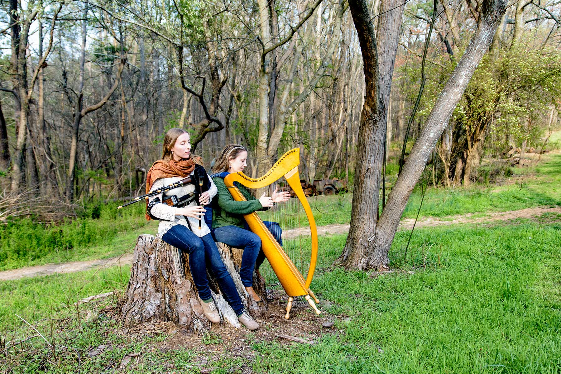 The Reel Sisters sitting on a tree stump. Rosalind is playing the Scottish smallpipes. Kelly is playing the harp.